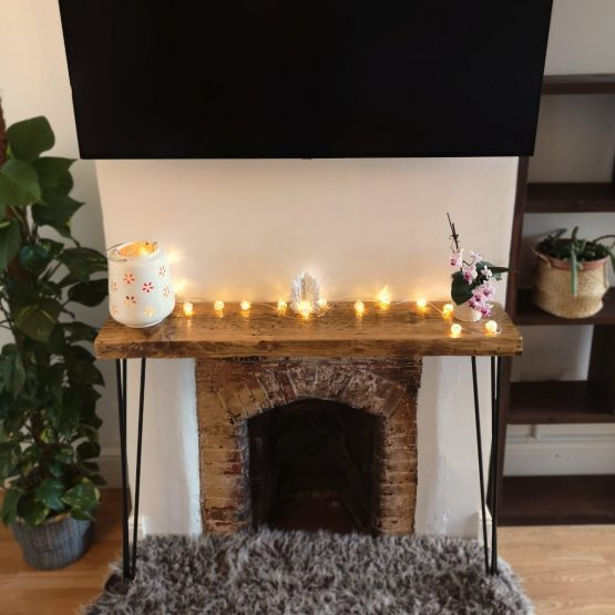 a rustic wood console unit above fireplace with fairy lights