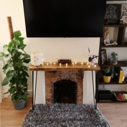 a rustic console unit above fireplace with orchid