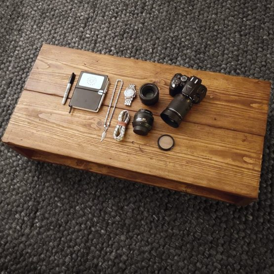 solid rustic coffee table with digital camera and notebook