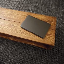 corner of a solid rustic coffee table with laptop