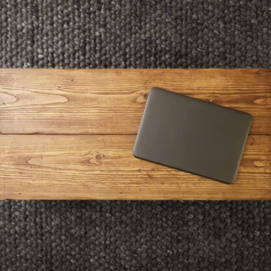 top down view of a solid rustic coffee table with laptop