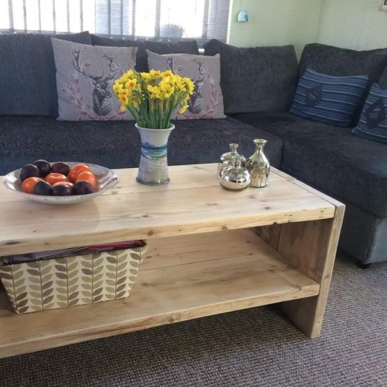 A rustic coffee table with grey sofa