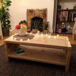 A rustic wooden coffee table with ornamental flowers and fairy lights