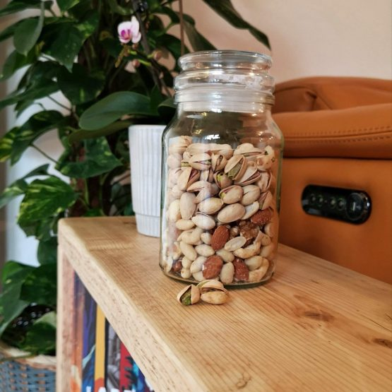 A reclaimed timber side table with pistachios on