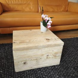 A useful reclaimed timber ottoman storage unit with orchid on top