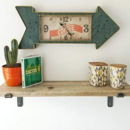 long stem steel brackets holding up rustic reclaimed wood shelf