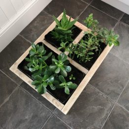A rustic reclaimed wood flower planter box with succulent plants