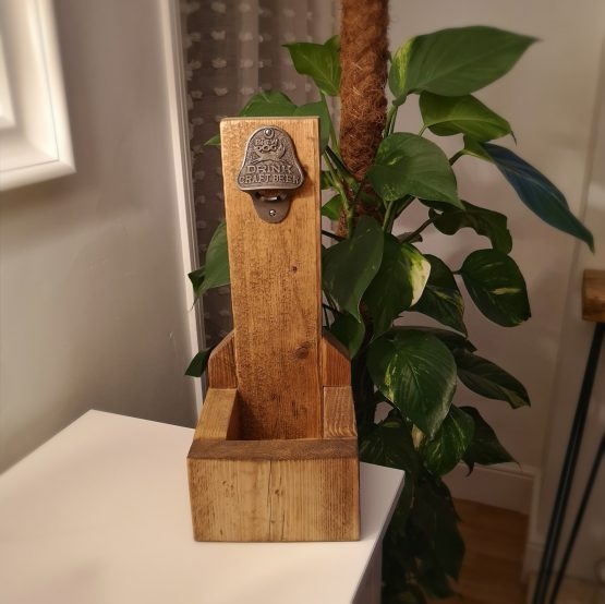 A rustic bottle opener for ale and beer. Green plant in background